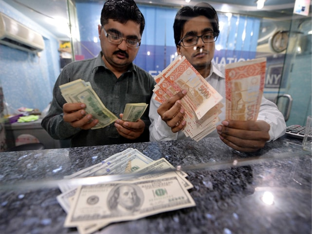 Currency dealers count rupees and US dollars in Islamabad.—File photo