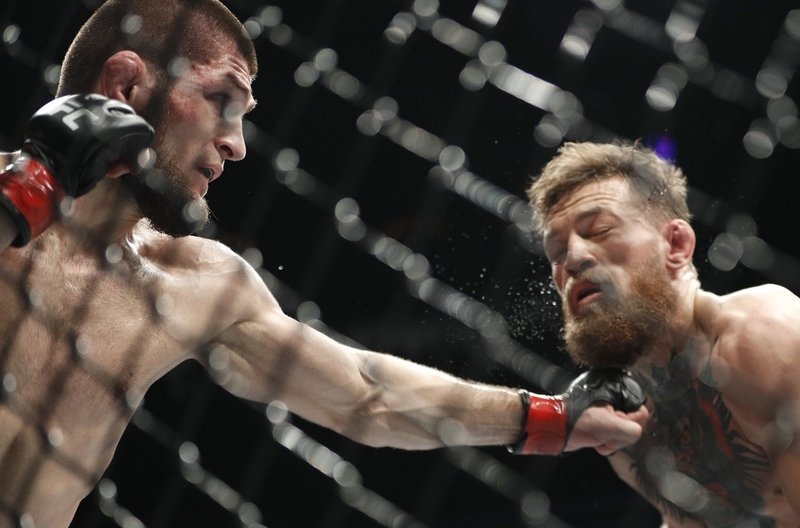 Khabib Nurmagomedov, left, punches Conor McGregor during a lightweight title mixed martial arts bout at UFC 229 in Las Vegas. ─AP