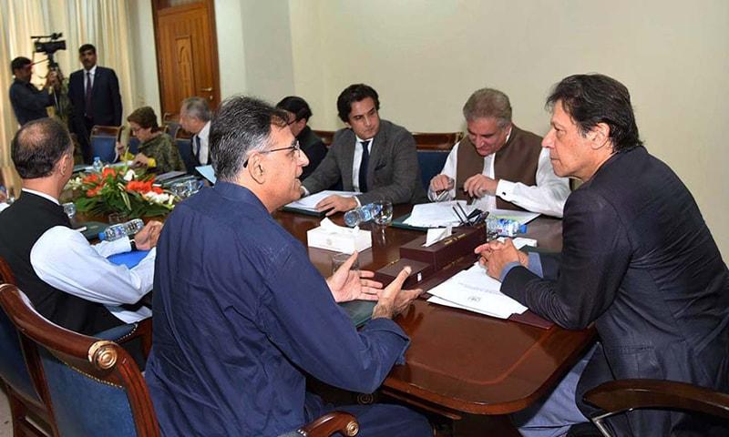 وزیر اعظم ہاؤس میں منعقدہ اعلیٰ سطح کے اجلاس کے دوران عمران خان وزیر خزانہ اسد عمر سے گفتگو کر رہے ہیں— فوٹو: اے پی پی
