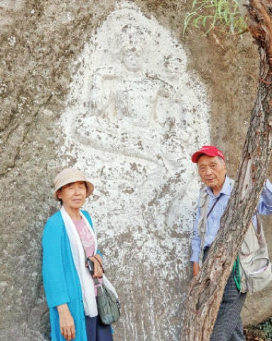 Dr So Gilsu with his wife at a rock-carved Buddha at Arab Khan Cheena, Swat. — Dawn