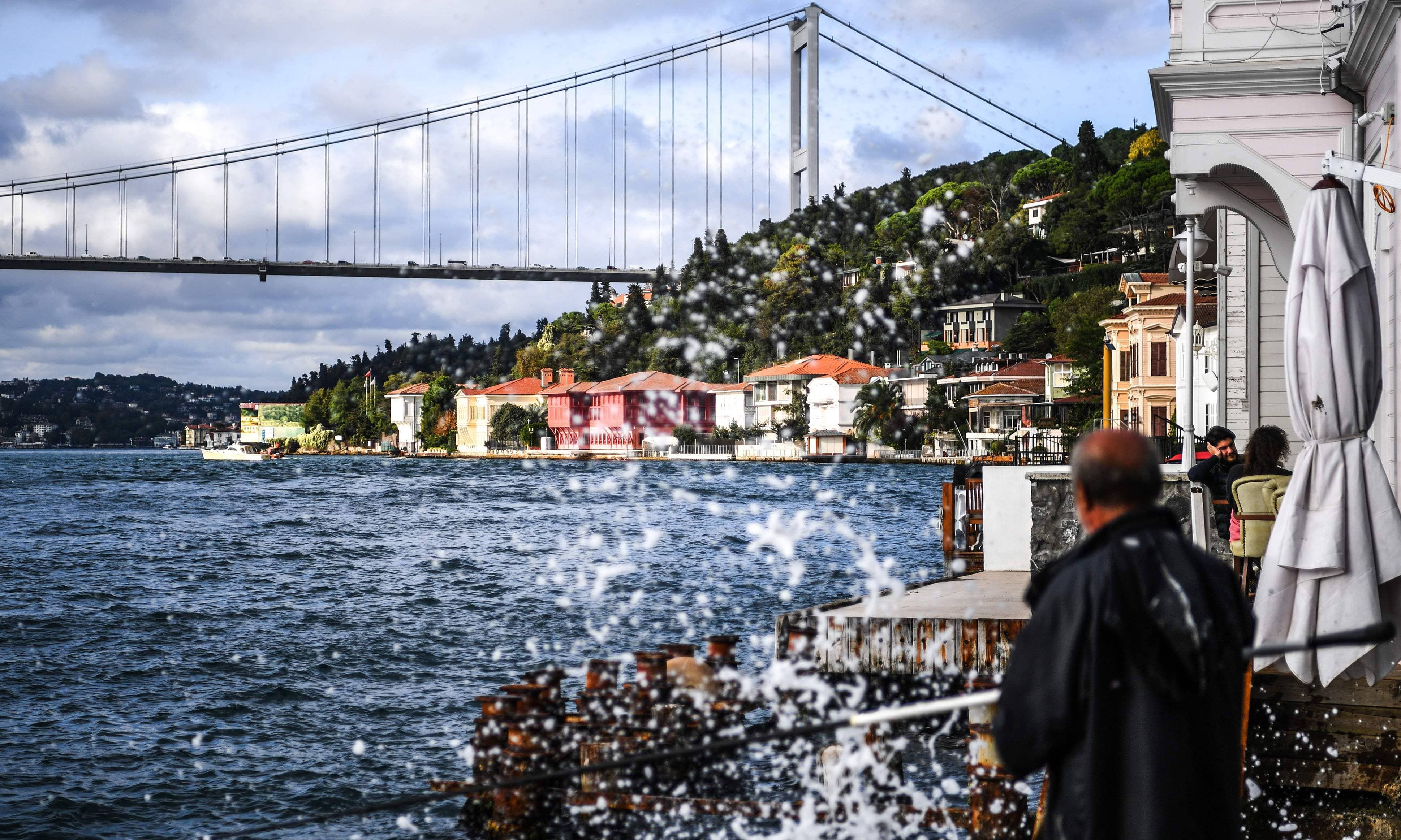 This photograph taken on September 28 shows a fisherman at work beside waterside mansions on the Bosphorus River coast on the Asian side of Istanbul. — Ozan Kose/AFP