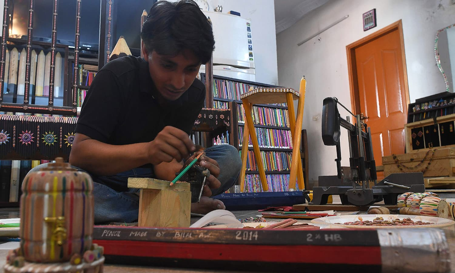 Bilal Asif works on his pencils artwork at his studio. — AFP