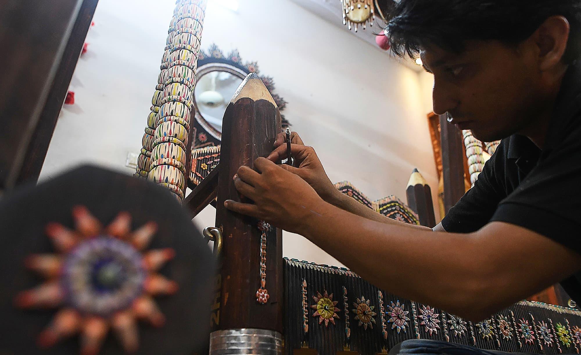 Artist Bilal Asif works on his studio in Karachi. -AFP