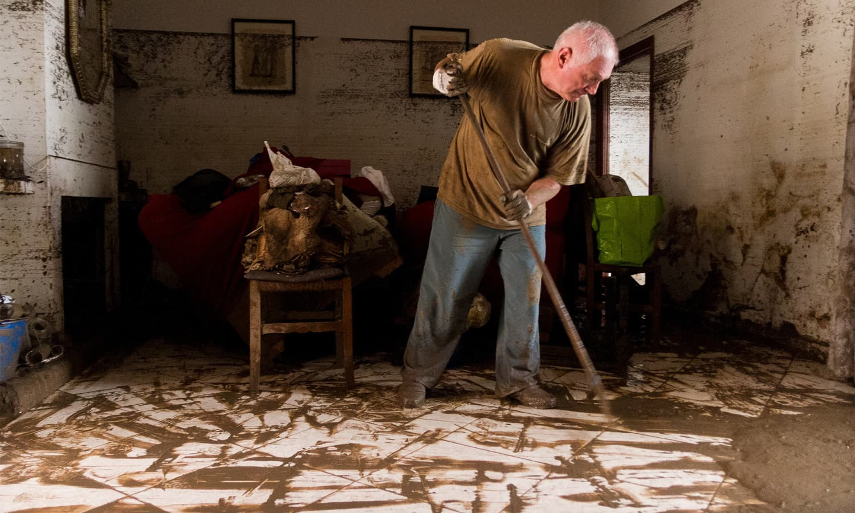ایک بزرگ شہری گھرسے کیچڑ صاف کررہے ہیں — فوٹو: اے ایف پی