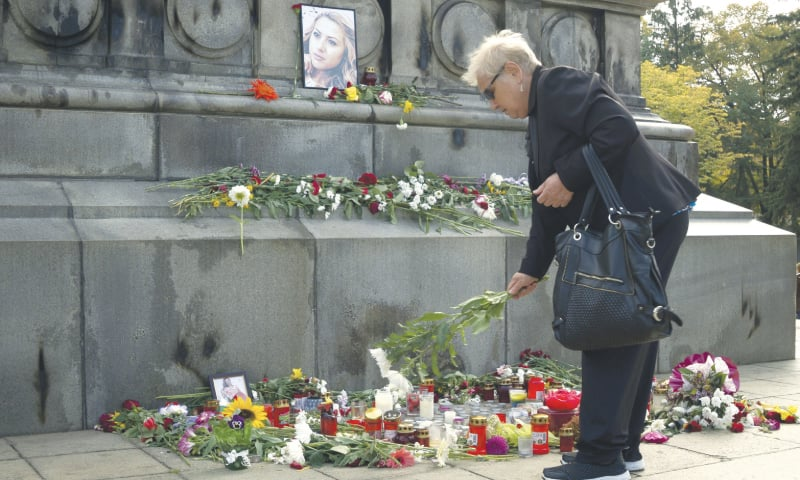 A woman places flowers around a makeshift memorial for television journalist Viktoria Marinova on Wednesday. — AP