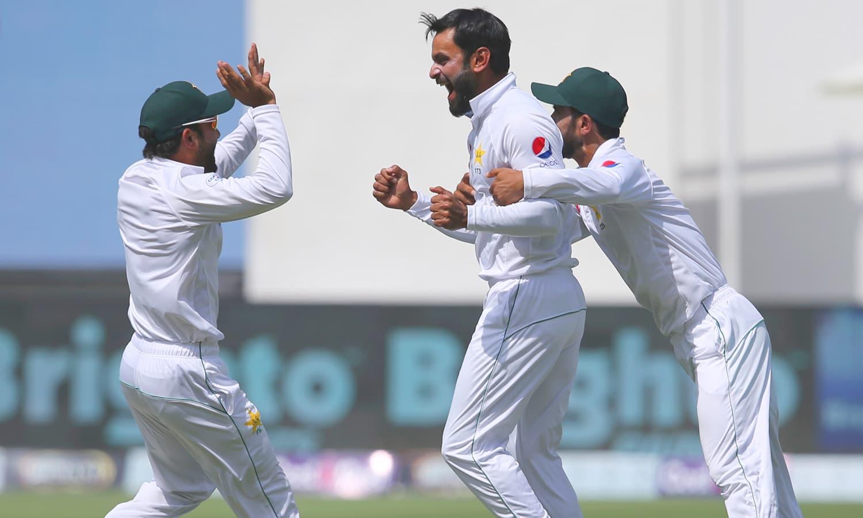 ٹریوس ہیڈ کی قیمتی وکٹ حاصل کرنے پر محمد حفیظ ساتھی کھلاڑیوں کے ہمراہ جشن منا رہے ہیں— فوٹو: اے پی