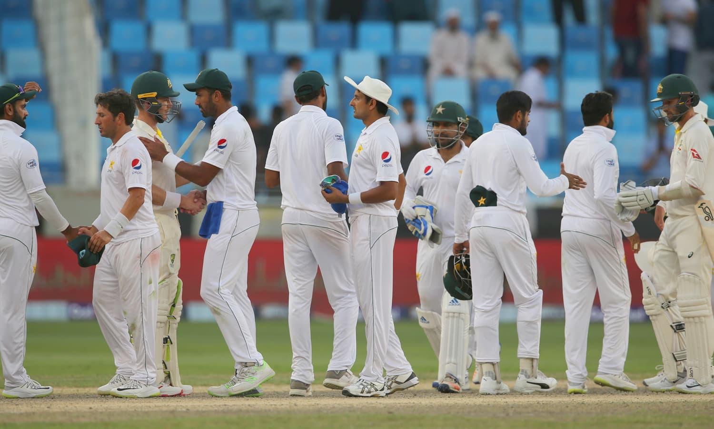 دبئی ٹیسٹ ڈرا پر ختم ہونے کے بعد پاکستان اور آسٹریلیا کے کھلاڑی مصافحہ کر رہے ہیں— فوٹو: اے ایف پی