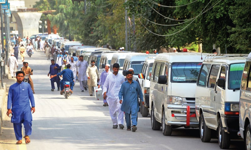 Commuters take a walk beside the parked vehicles as Peshawar transporters went on strike against government failure to remove  illegal bus stands and CNG price hike. — Photo by Shahbaz Butt