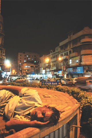 A HOMELESS man sleeps on the pavement in the Saddar area.—Stephan Andrew / White Star