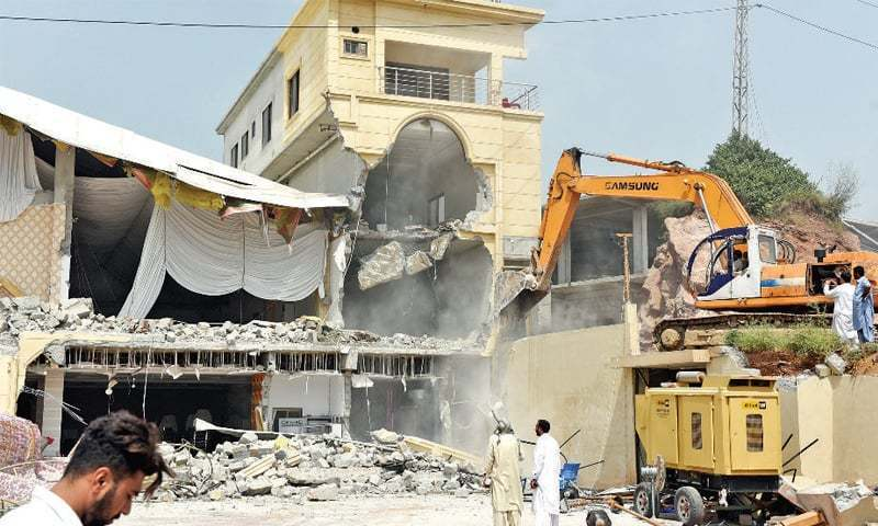 A marquee is demolished along Kashmir Highway during CDA's operation in Islamabad in September. — File Photo