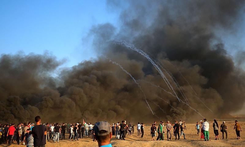 اسرائیل اور غزہ کی سرحد پر فلسطینیوں کے احتجاج کے دوران جا بجا دھویں کے بادل چھائے ہوئے ہیں— فوٹو: اے ایف پی