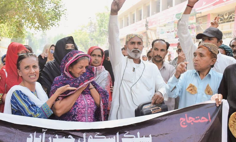 A TEACHER among the protesters narrates her family's woes outside the Hyderabad Press Club on Saturday.—Dawn