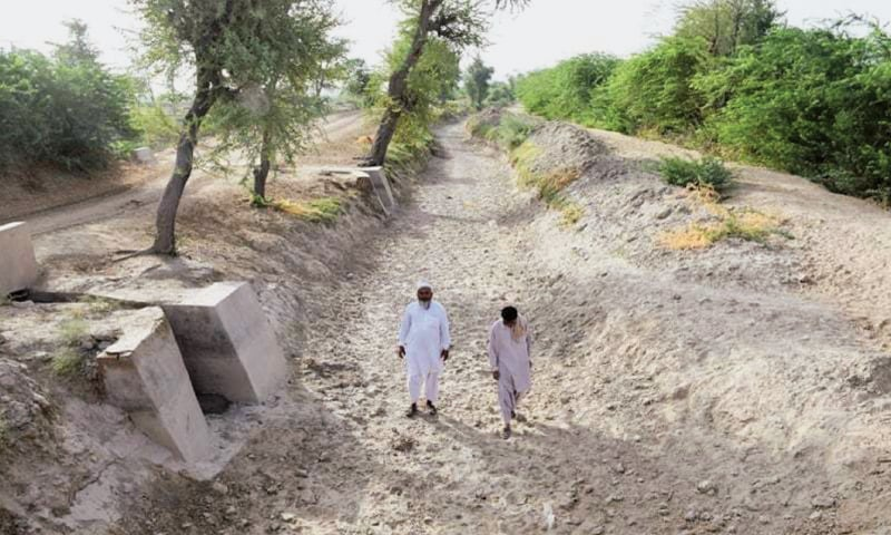 Villagers walk along a dried up canal near Badin. The disrupted water supply from the Indus has played havoc with this year's planting of crops | Dawn File Photo