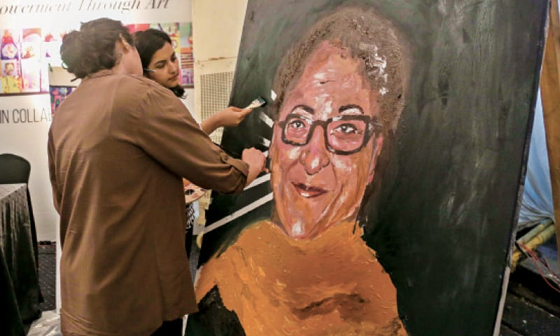 Artists paint Asma Jahangir's picture at the conference. — White Star