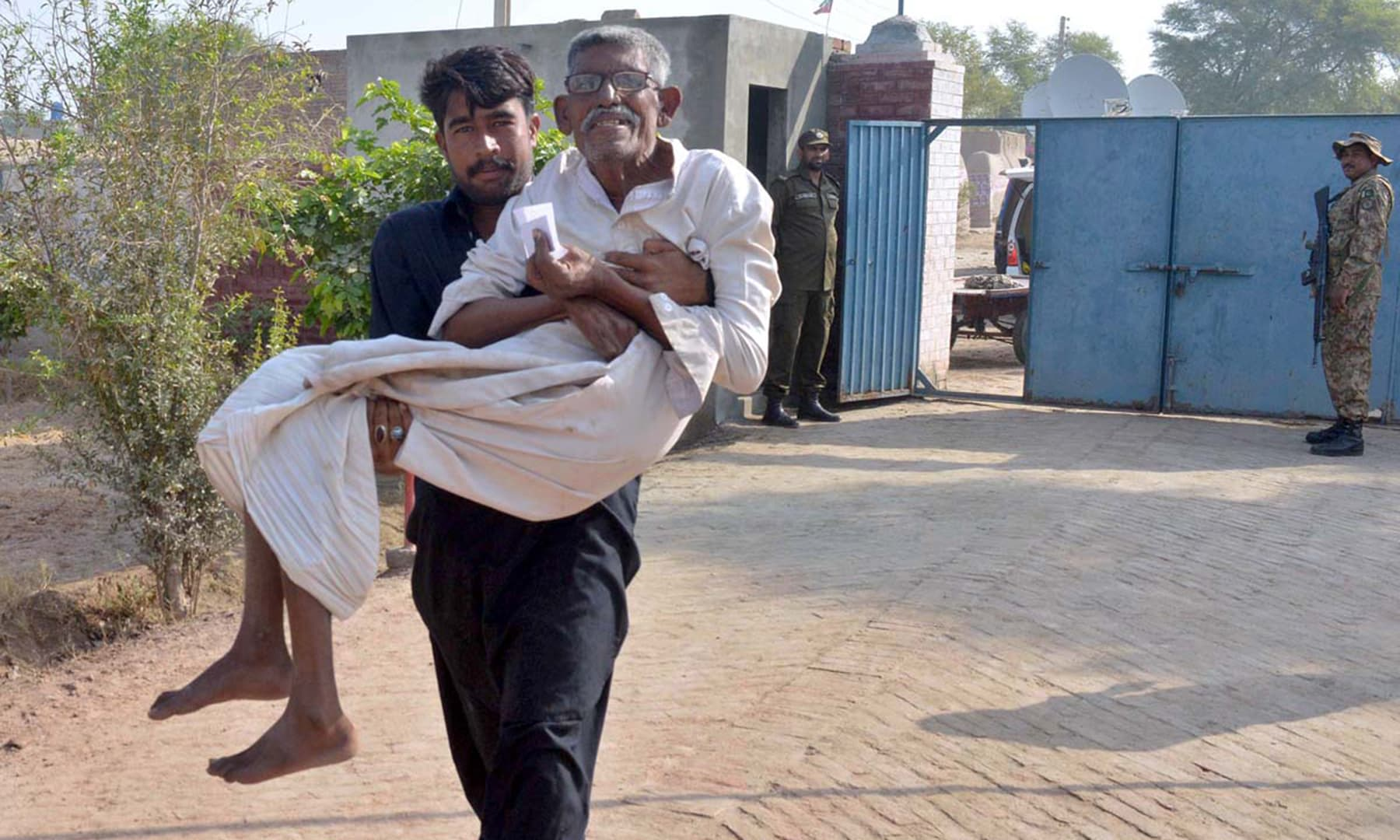 A man carrying his elderly father for casting vote for PP-222 by-election in Naseer Pur. —APP