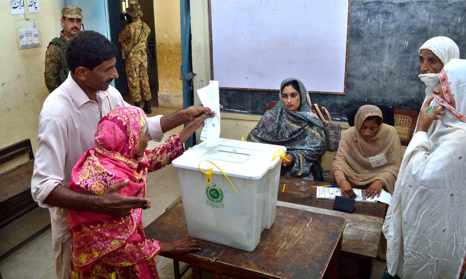 Relative of a senior citizen helping her to cast her vote at a Naseer Pur PP-22 polling station. —APP