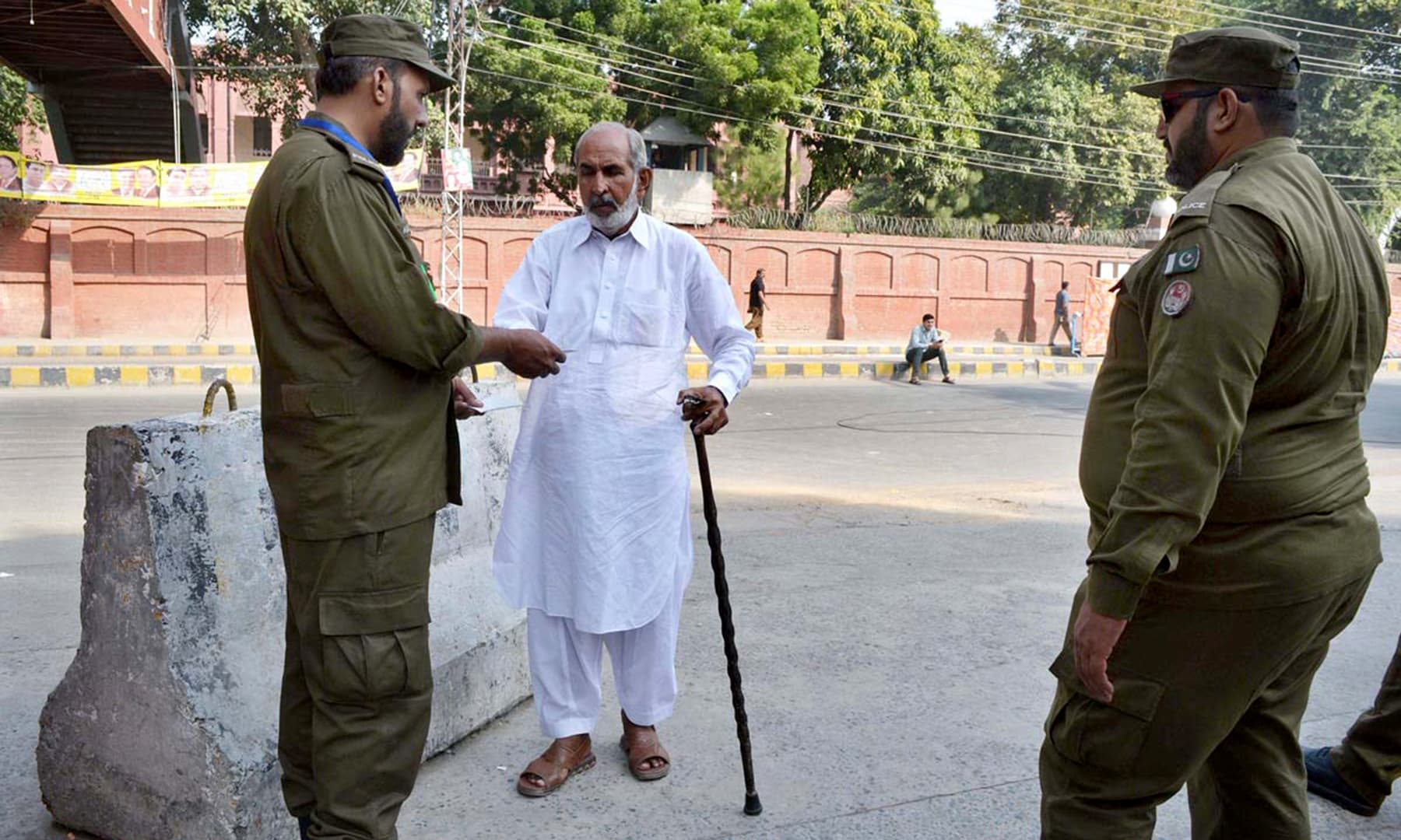 Security official checking identity of a citizen before he enters a polling station in Lahore. —APP