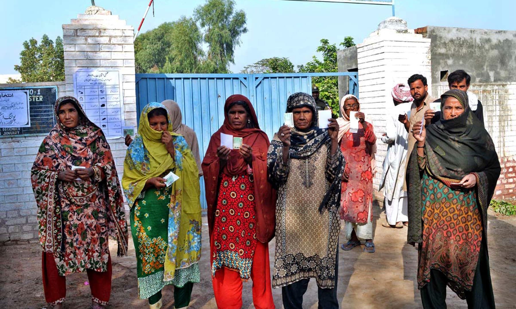 Women showing their Identity cards after casting vote outside a polling station in Jalapur Pirwala. —APP