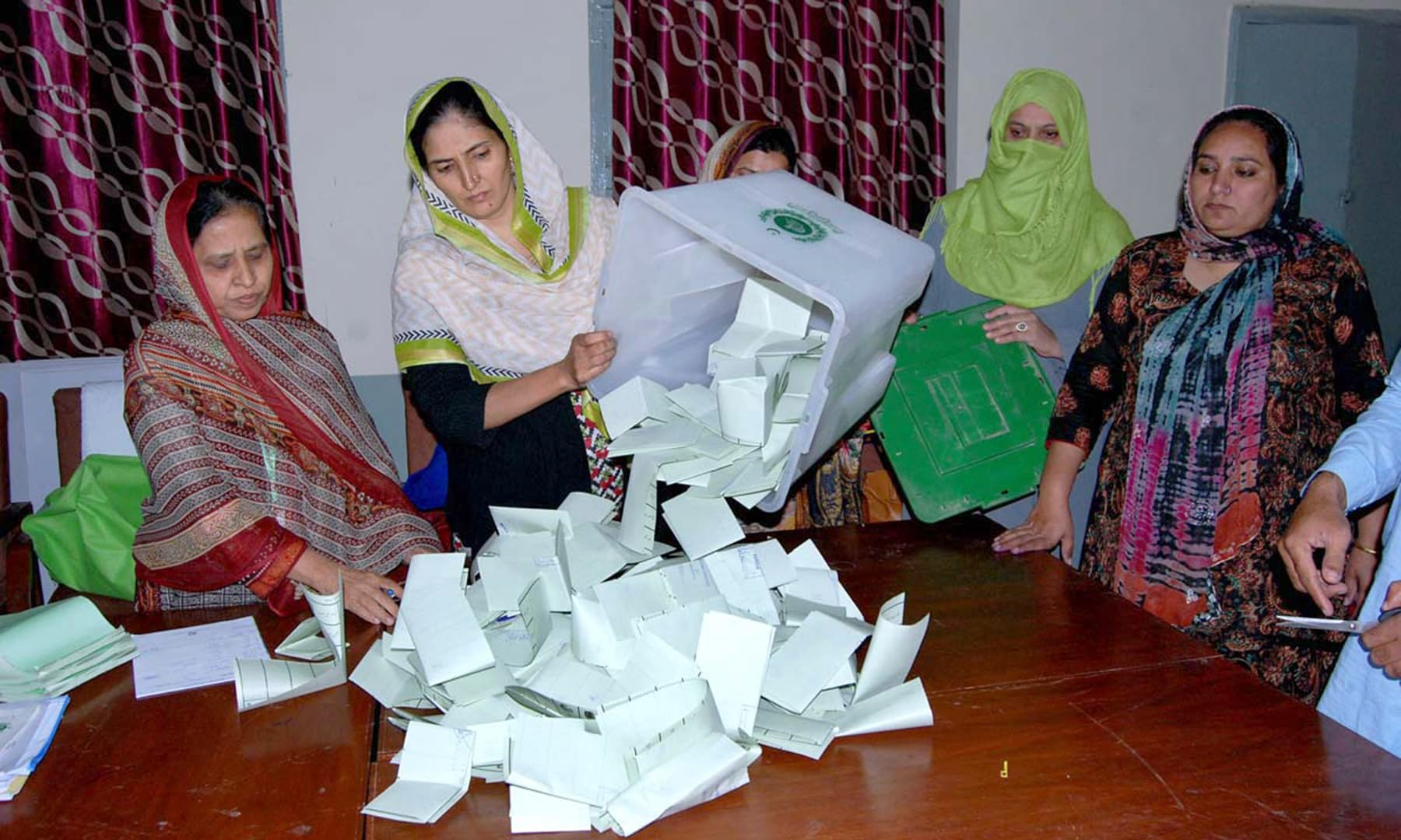 Polling officials open the ballot box at an Islamabad polling station to begin counting votes. —APP