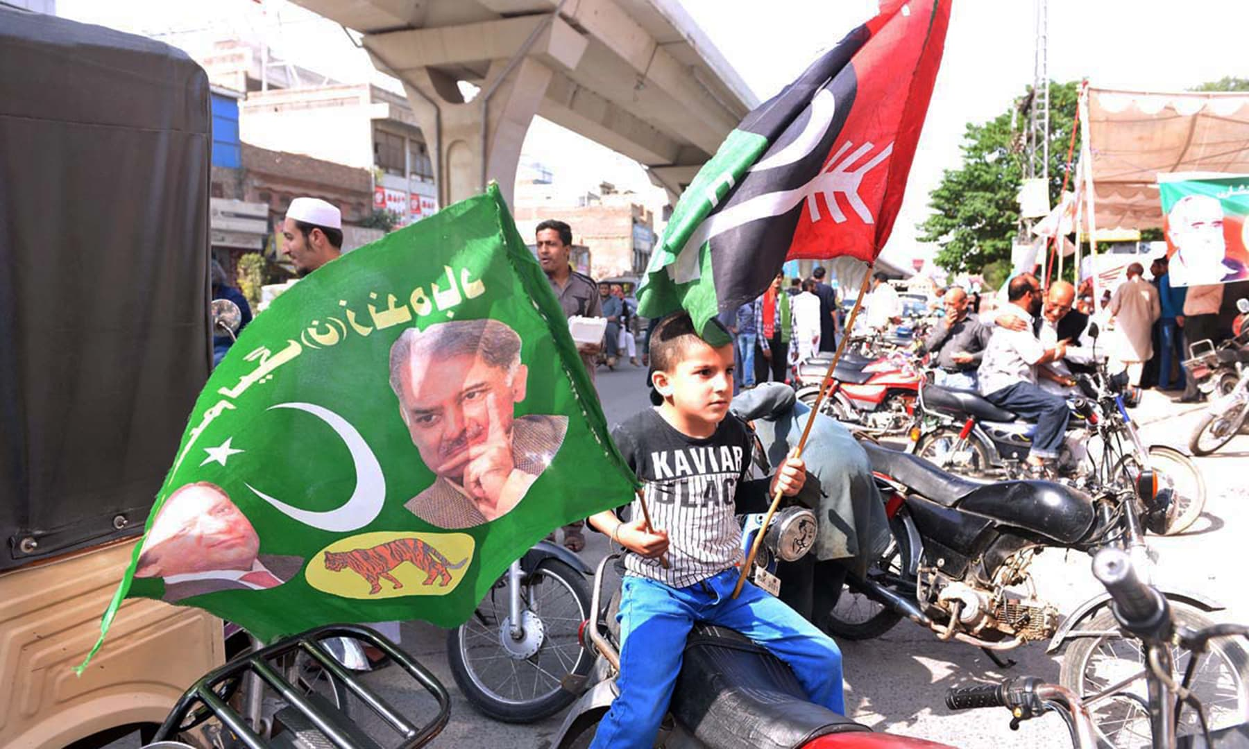 A youngster holding flags of political parties outside polling station in Rawalpindi. —APP