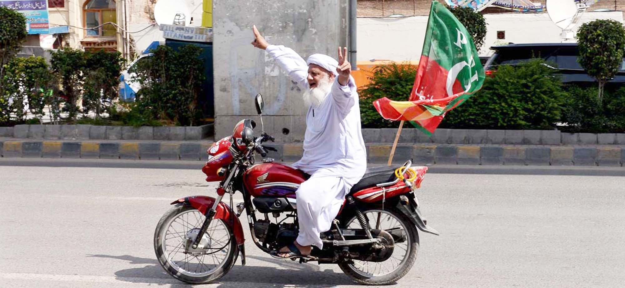 APP35-14 RAWALPINDI: October 14 – An elderly person on the way on his motorcycle with political party flag during by-election. APP photo by Abid Zia  —