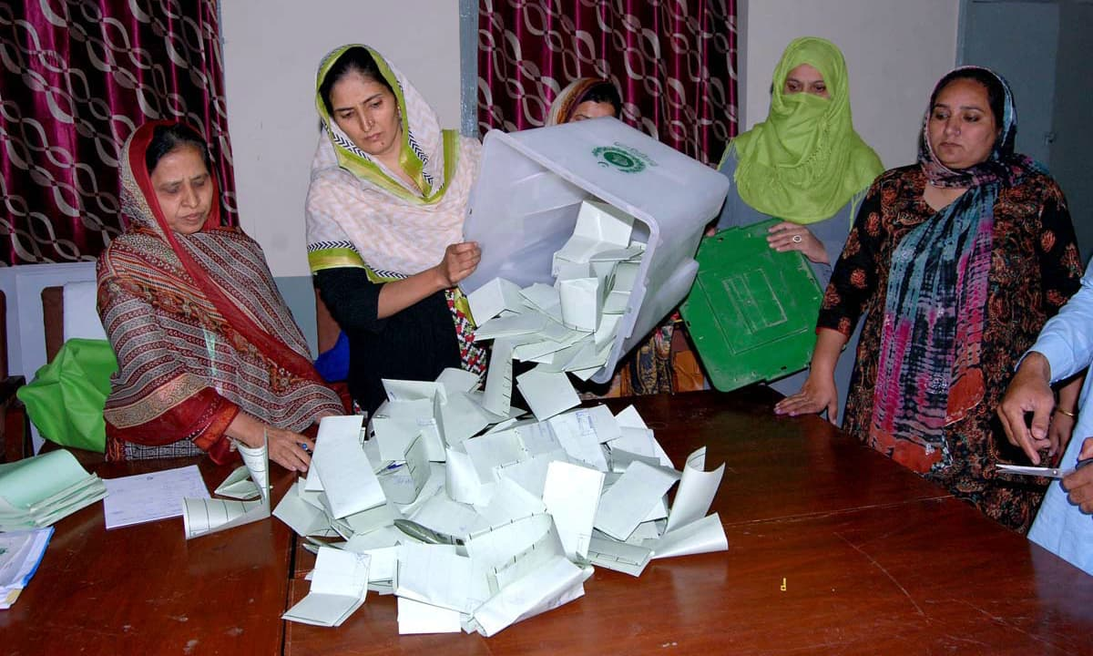 Polling official opens the ballot box at a polling station in Islamabad. —APP