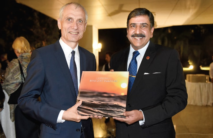 Swiss Ambassador Thomas Kolly and NDMA Chairman Lt Gen Omar Mehmood Hayat hold a copy of A Journey through Resilient Pakistan at the book launch in Islamabad.