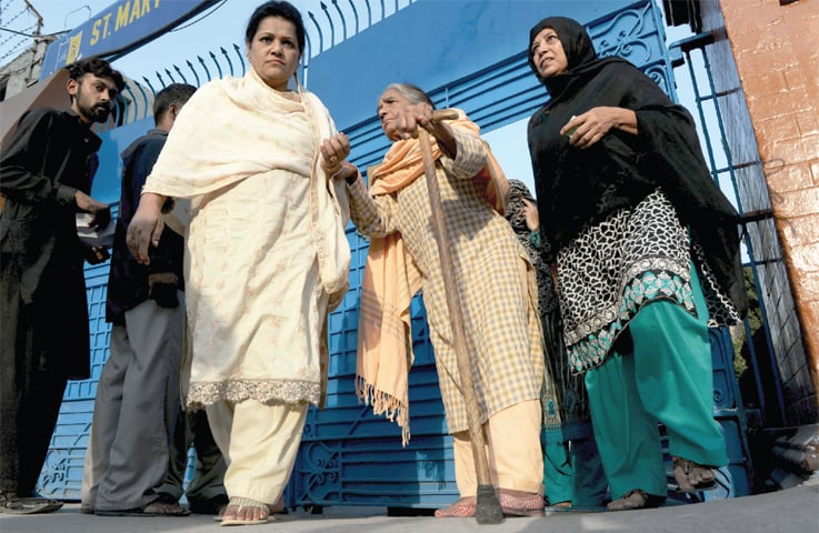 Women arrive at a polling station in St Mary's School on Murree Road to cast their vote for NA-60 seat on Sunday. — Photo by Mohammad Asim