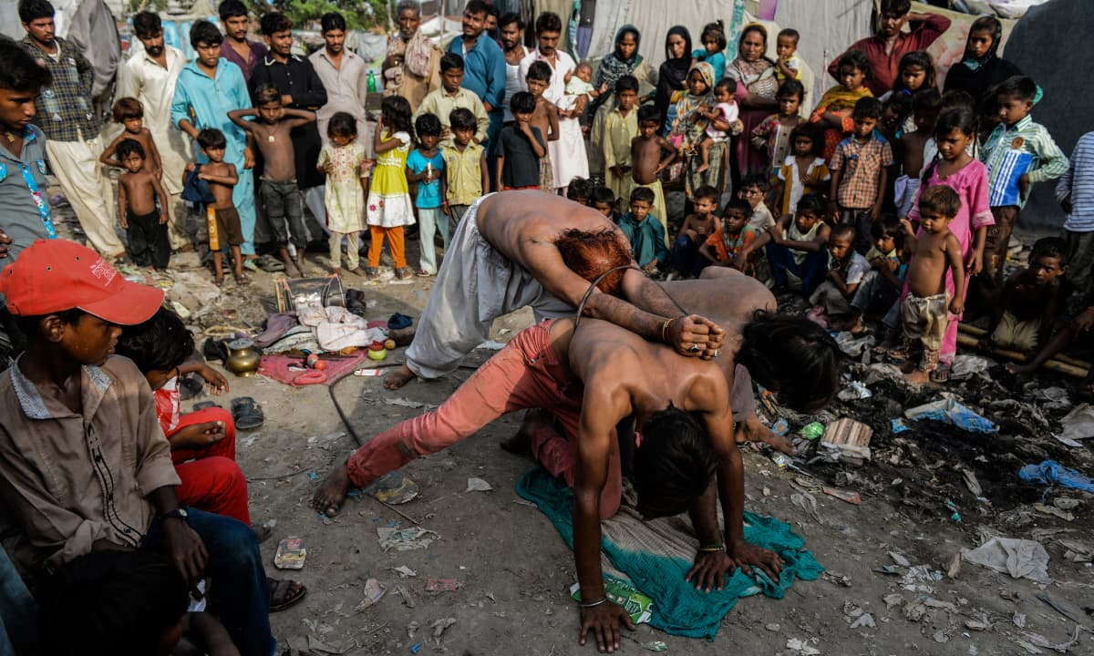Bahar Ali (centre) attempting to pass through a metal ring, the final act of a performance in a shanty town off Multan Road in Lahore