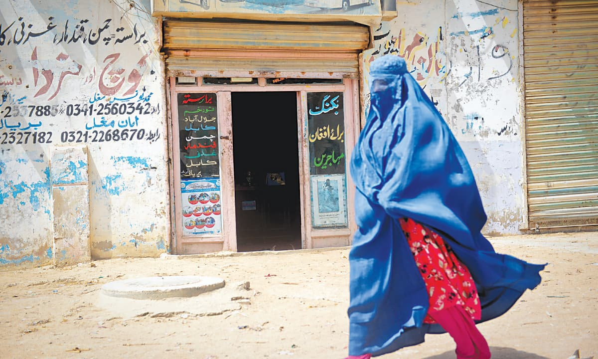 THE modest abodes of Bengali families in Mohammadi Colony, better known as Machhar Colony, off Mauripur Road. On the right, an Afghan woman walks past the booking office meant for refugees returning to Afghanistan.—White Star