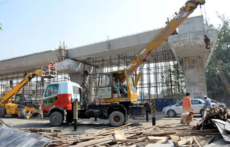 PESHAWAR: Labourers use heavy machinery for construction of the Bus Rapid Transit (BRT) project.—Online