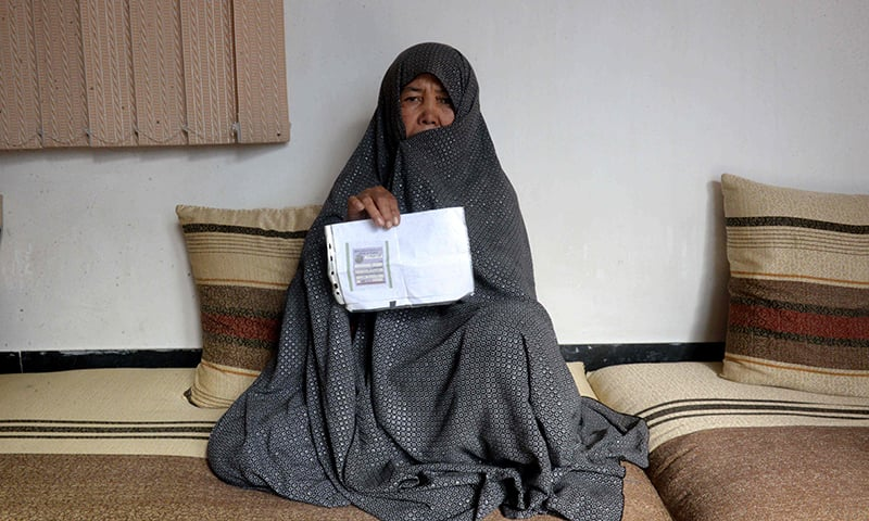 Afghan housewife Fatimah, 55, poses for a picture as she holds her ID card or Tazkira registered to vote in the upcoming parliamentary election, at her House in Mazar-i-Sharif. — AFP