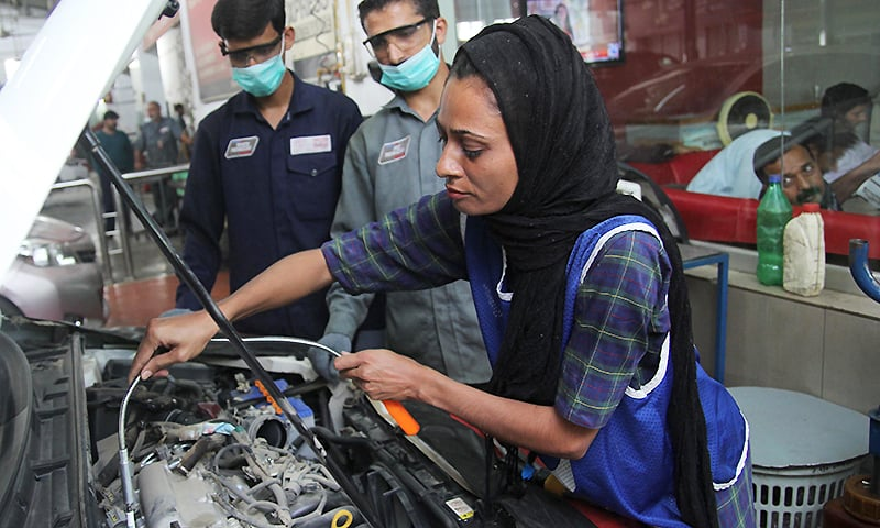 Mechanic Uzma Nawaz, 24, fixes a car at an auto workshop in Multan. — AFP
