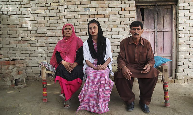 Uzma sits with her parents at their home in Duniyapur. ─ AFP