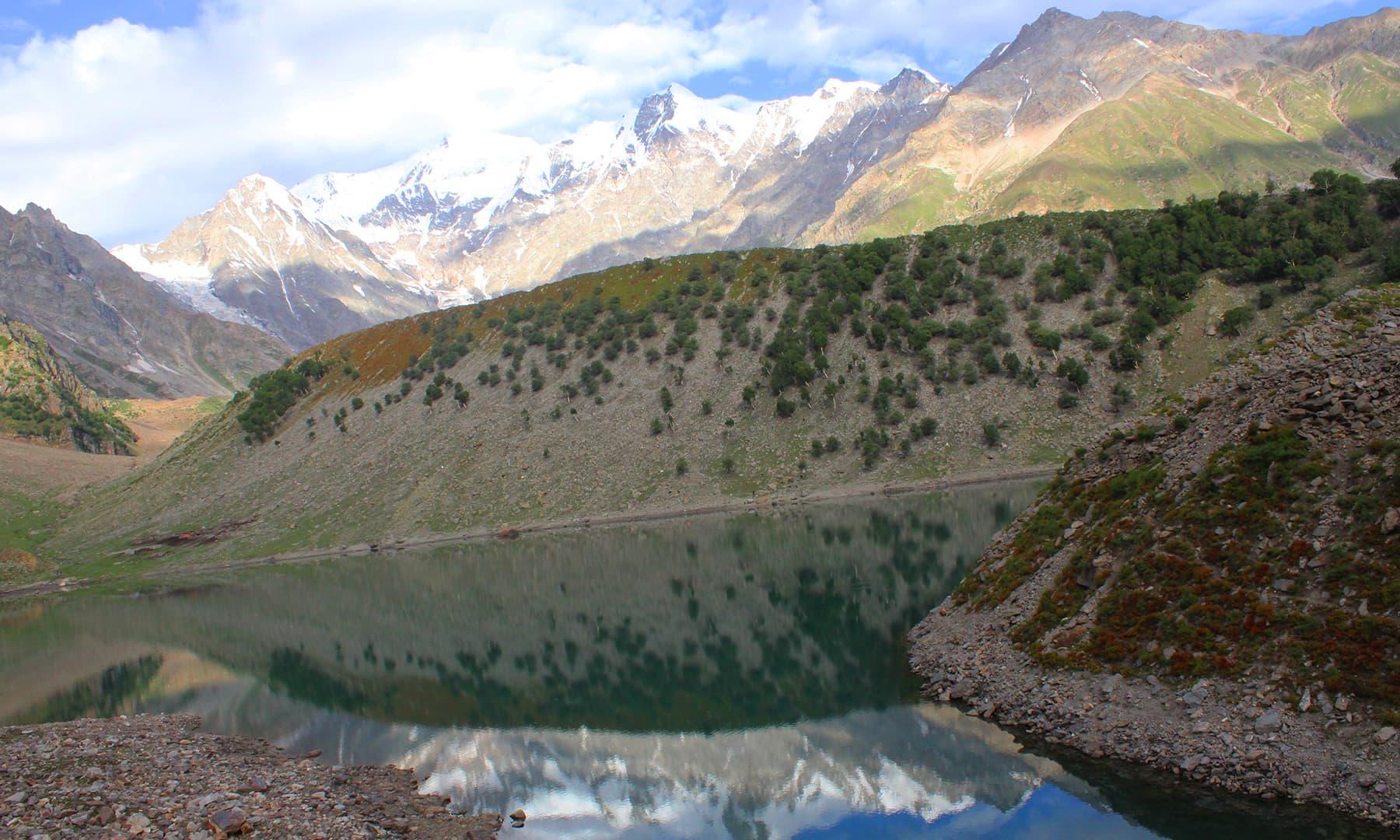 راما جھیل، قریب ایک چھوٹا سا پہاڑ، پیچھے نانگا پربت اور جھیل کے پرسکون پانیوں کا ایک منظر—تصویر عظمت اکبر