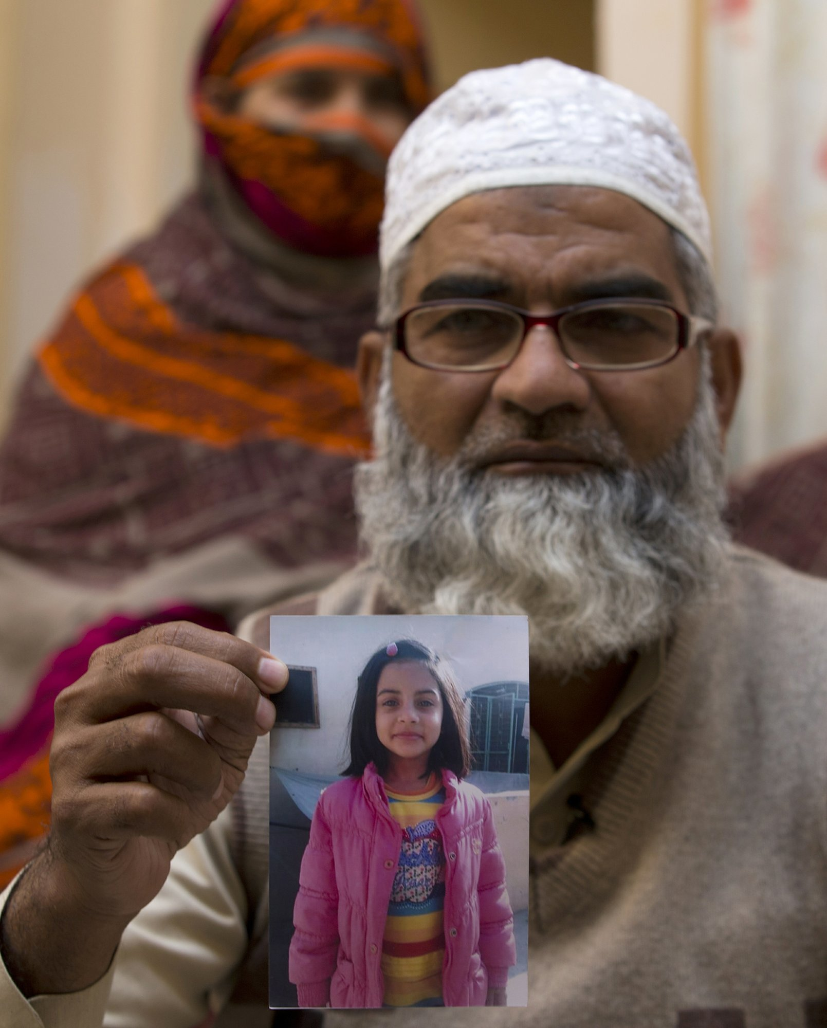 In this Jan 18 file photo, Mohammed Amin Ansari holds a picture of his daughter Zainab as her mother Nusrat stands in the background, in Kasur. ─ AP
