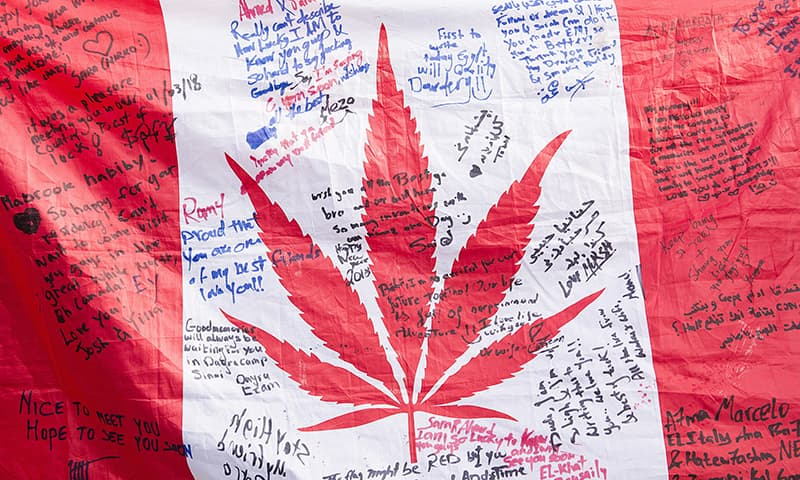 People hold up a Canadian flag with a marijuana logo on it outside a government cannabis store in Montreal on Oct 17, 2018. — AP