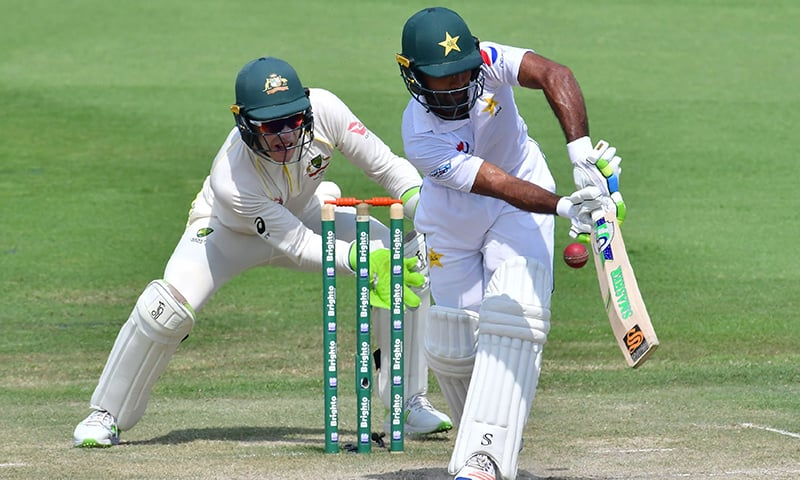 Pakistan cricketer Asad Shafiq (R) plays a shot as Australian wicketkeeper Tim Paine looks on during day three of the second Test cricket match in the series between Australia and Pakistan at the Abu Dhabi Cricket Stadium in Abu Dhabi on October 18. — AFP