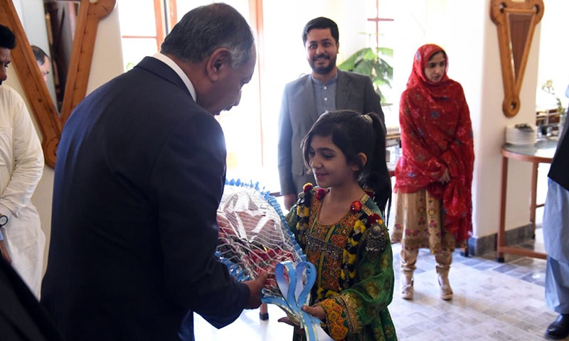 Balochistan Governor retired Justice Amanullah Khan Yasinzai receives a bouquet from a child. — Photo by author