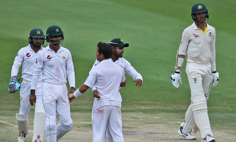مچل اسٹارک کو آؤٹ کرنے کے بعد پاکستانی کرکٹر یاسر شاہ کو مبارکباد دے رہے ہیں— فوٹو: اے پی