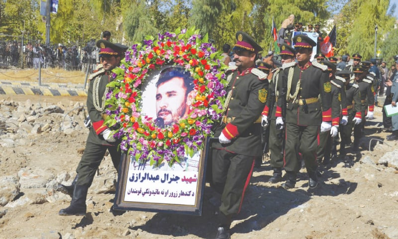 GUARDS carry a portrait of Kandahar police chief Gen Abdul Raziq at his funeral on Friday.—AP