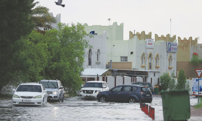Doha: Motorists drive through a flooded street following heavy rains on Saturday.—AFP