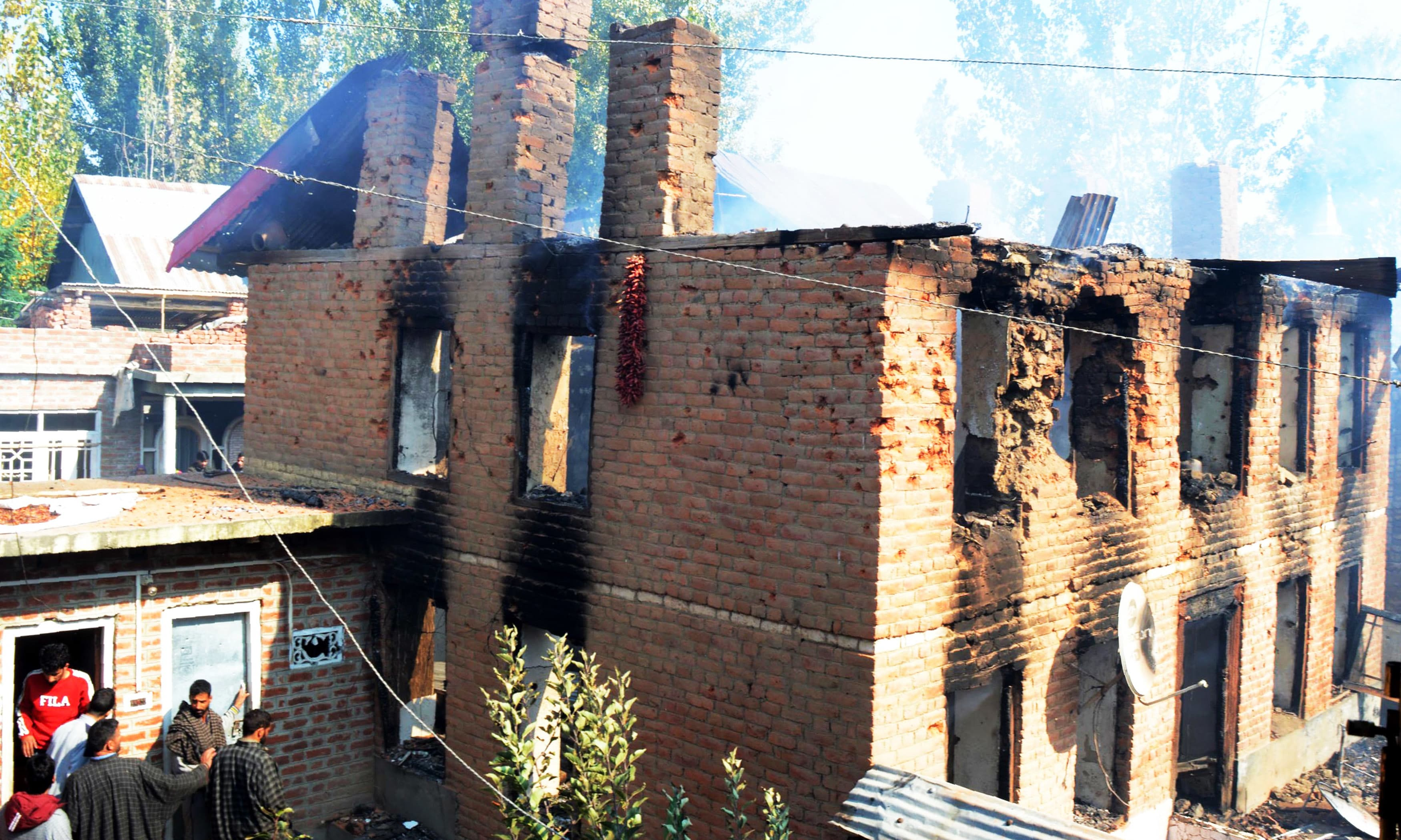 Residents look on as smoke billows from a house after a gunfight with Indian forces in Kulgam town. —AFP