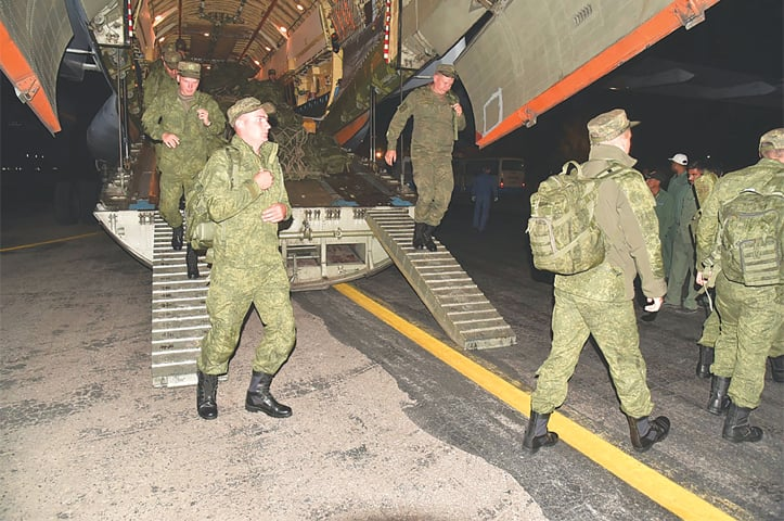 RUSSIAN troops come out of their plane at a military base at an undisclosed location.—AFP