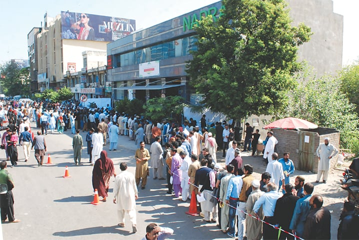 ISLAMABAD: People wait for their turn in front of the Nadra office on Monday.— Mohammad Asim / White Star