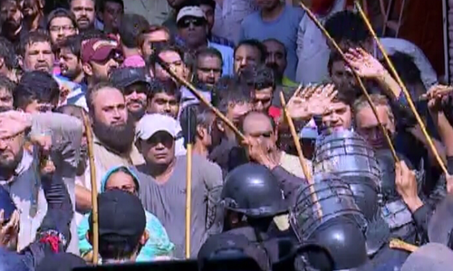 Baton-wielding policemen in riot gear push back protesters in Karachi's Pakistan Quarters area. ─ DawnNewsTV