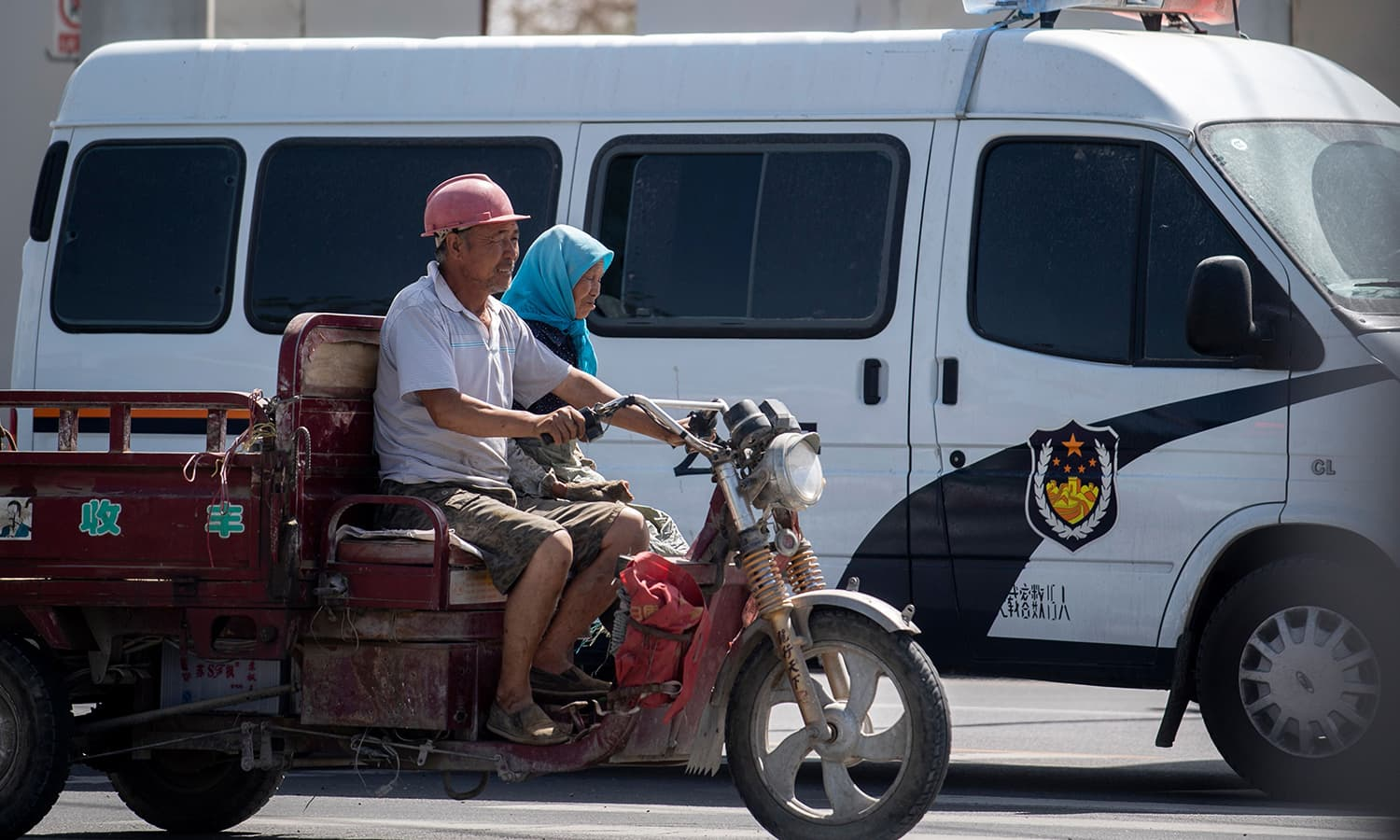Local Muslims passing a police car in their vehicle in Hotan in China's Xinjiang Uighur Autonomous Region. — AFP