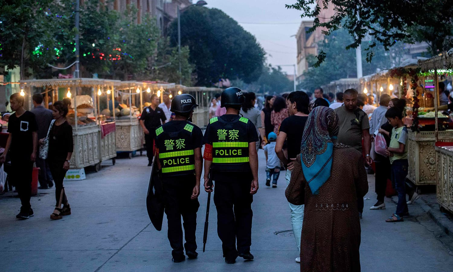 Police patrol in a night food market near the Id Kah Mosque in Kashgar in China's Xinjiang region, a day before the Eidul Fitr holiday. — AFP