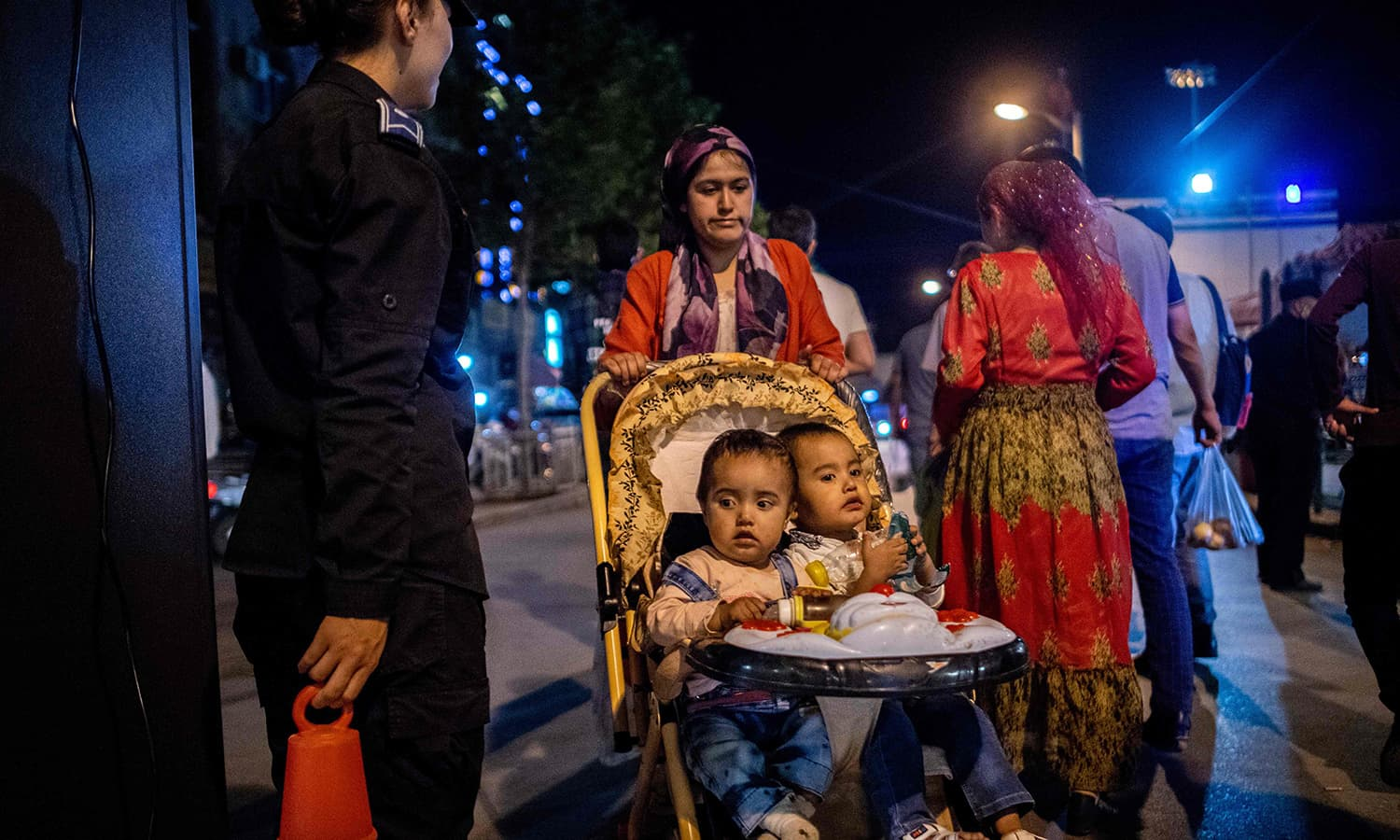 A woman pushes her children in a stroller through a police checkpoint at a night food market near the Id Kah Mosque in Kashgar in China's Xinjiang in this file photo. — AFP