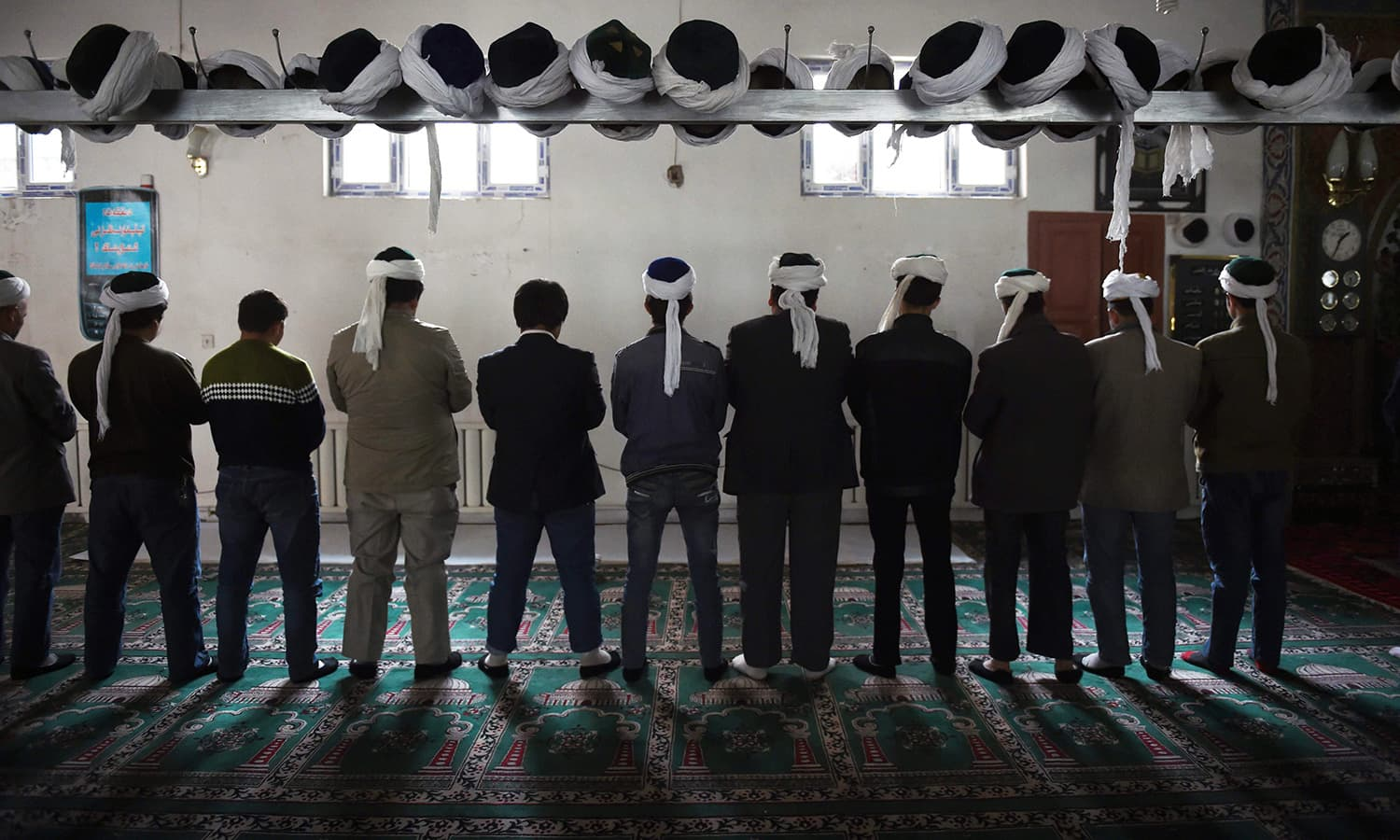 Uighur men pray in a mosque in Hotan, in China's western Xinjiang region in this 2015 file photo. — AFP